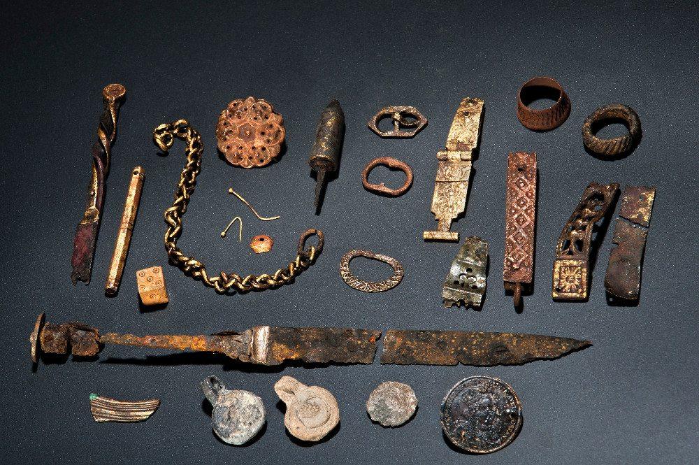 Das rätselhafte Fundensemble enthält verschiedene, zum Teil vergoldete Metallobjekte, darunter, eine Buchschliesse und zwei Messer.