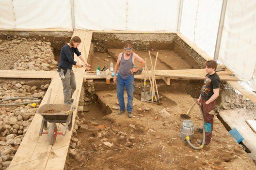 Die Archäologin Alissa Cuipers (links) erklärt zwei Ausgräbern das weitere Vorgehen bei der Freilegung der römischen Strukturen.
