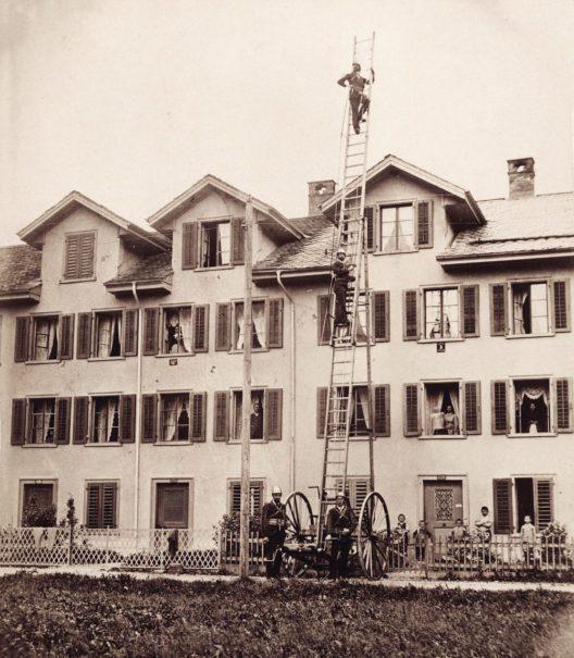 Mollis, Spinnereistrasse 32–36, Südwestfassaden. 1884–1887 von Baumeister Zacharias Schindler erstellte Häuserzeile, die von den Mitarbeitern der Spinnerei & Weberei Mollis genutzt wurde. Feuerwehrübung um 1900. (Bild: OMM 1262)