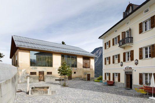 Das ehemalige Anwesen der Familie Carisch: Die umsichtig umgebaute Scheune und die neu bespielte Villa bilden mit dem aufgefrischten Vorplatz ein charaktervolles Ensemble. (Bild: Beutler/Keystone)