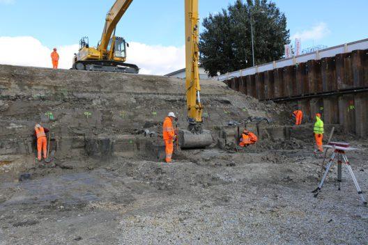 Eine Mitarbeiterin des Archäologischen Dienstes des Kantons Bern legt fast 6000-jährige Pfähle einer Palisade frei.