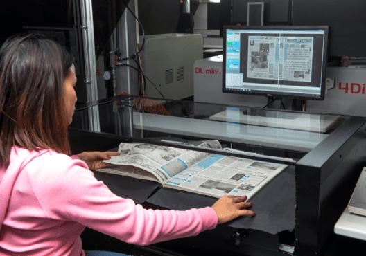 """Die Mitarbeiterin einer Scanfirma scannt einen Band des """"Thuner Tagblatts"""". Dabei blättert sie die Seiten von Hand um, fährt die Glasplatte auf das Papier, damit sie Seiten flach liegen, und fotogafiert immer eine Doppelseite."""