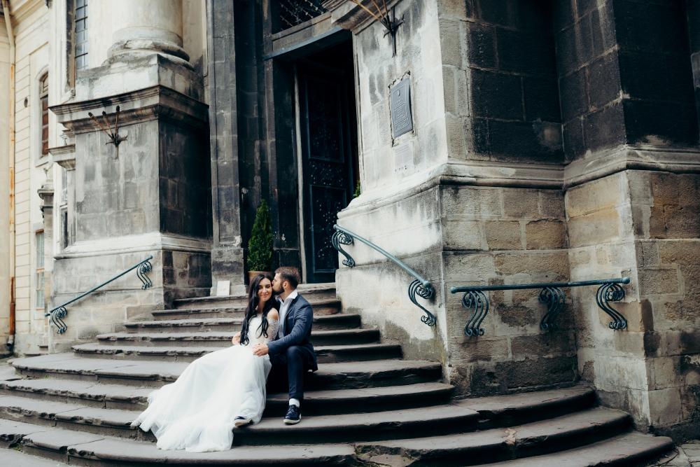 Hochzeitspaar sitzt auf einer Treppe vor einer Barocker Kirche