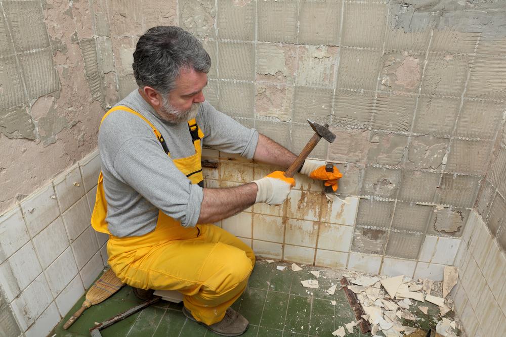 Mann schlägt alte Fliesen von der Wand